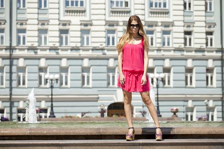 vestido corto: Joven y bella mujer rubia en vestido corto de color rojo posando al aire libre en un d�a soleado Foto de archivo