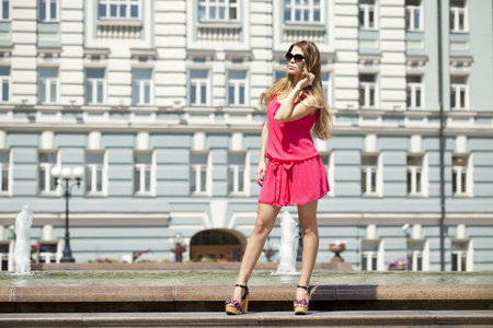 short dress: Young beautiful blonde woman in red short dress posing outdoors in sunny weather Stock Photo