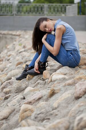 river bank: Young beautiful brunette girl in blue jeans sitting on the rocks on the river bank