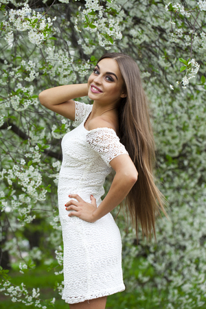 vestido blanco: Beautiful young brunette woman in white dress against the background spring flowers trees