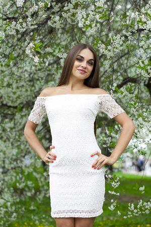 vestido blanco: Hermosa mujer morena con vestido blanco contra el fondo flores de primavera �rboles
