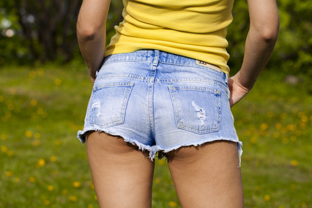 sexually: Part of the body, torn blue jeans shorts for women on the background summer street