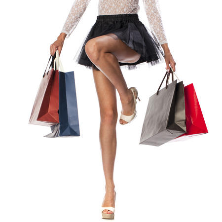 Part body, beautiful female slender legs. Sexy girl holding a paper shopping bags, isolated on white background Stok Fotoğraf