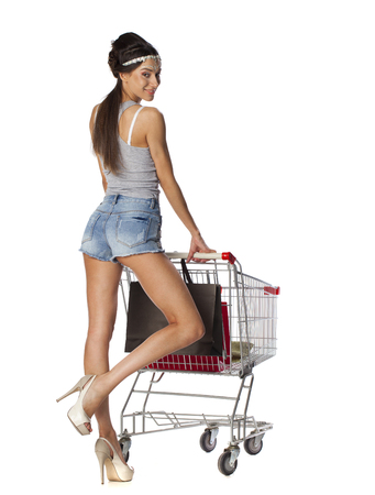 woman shopping cart: Smiling brunette woman posing next to an empty shopping cart isolated on white background