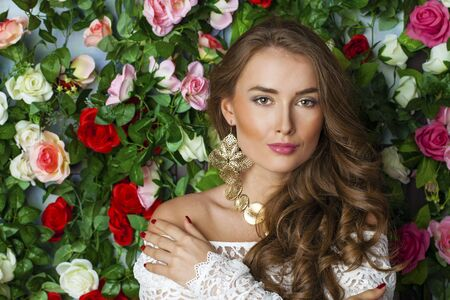 beautiful rose: Beautiful young brunette woman in classy white dress on flower wall background Stock Photo
