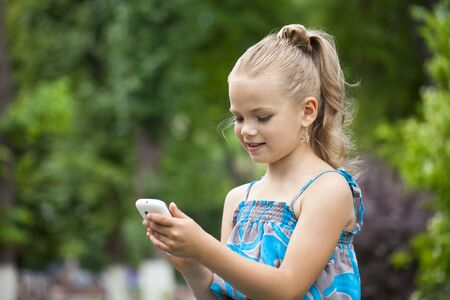 female child: Little girl holding a cell phone and reads the message on the background of summer park