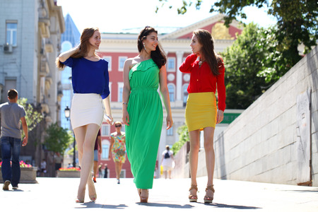 colorful dress: Three Beautiful young women in colorful dress walking in summer street Stock Photo