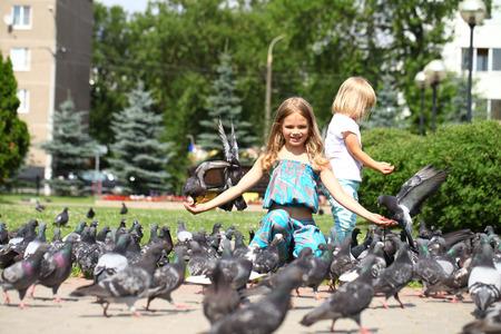only 3 people: Happy little girls feeding doves, against green sunner park Stock Photo