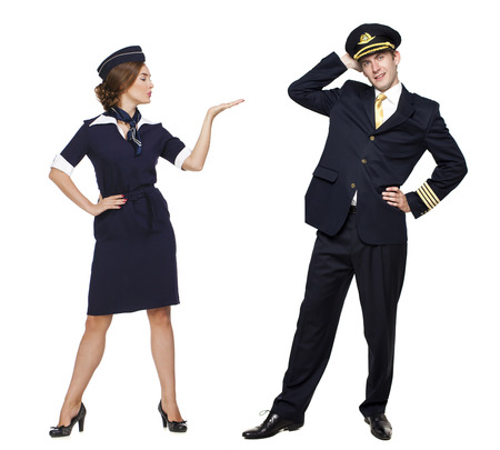 flights: Captain of the aircraft and a beautiful flight attendant in a dark blue uniform, isolated on white background Stock Photo