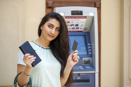 withdrawing: Brunette young lady using an automated teller machine . Woman withdrawing money or checking account balance Stock Photo