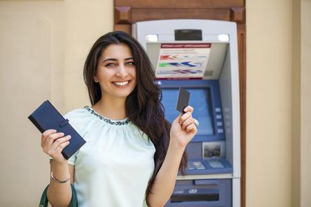 efectivo: Brunette señora joven que usa un cajero automático. Mujer que retira el dinero o saldo de la cuenta de cheques