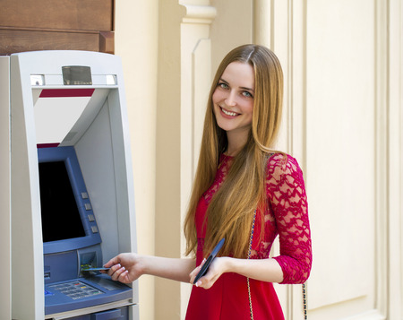 automated teller: Blonde lady using an automated teller machine . Woman withdrawing money or checking account balance