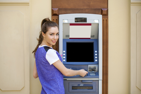 checking account: Brunette young lady using an automated teller machine. Woman withdrawing money or checking account balance Stock Photo