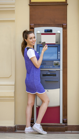 cash dispenser: Brunette young lady using an automated teller machine. Woman withdrawing money or checking account balance Stock Photo