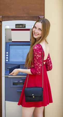 checking account: Blonde lady using an automated teller machine . Woman withdrawing money or checking account balance