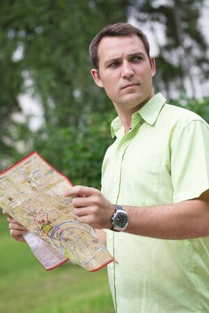 looking around: Young male tourist with map in hand looking around. Tourist map of the city of Moscow, Russia (no trademark)