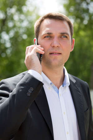 englishman: Close up, young businessman calling by phone in summer street