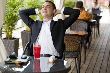 englishman: Portrait of a young business man in a dark suit and white shirt sitting in summer cafe Stock Photo