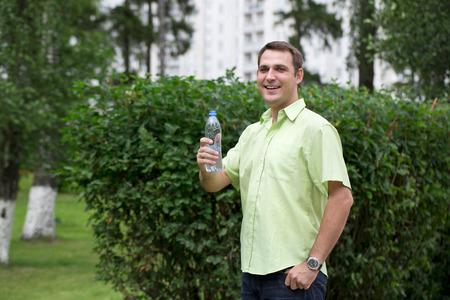 man drinking water: Handsome man drinking water in summer park