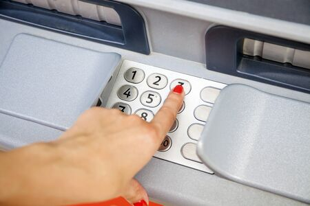 technology transaction: Female arms, ATM - entering pin Stock Photo