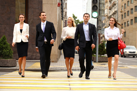 confidently: Successful Team of five business people confidently striding along the summer street