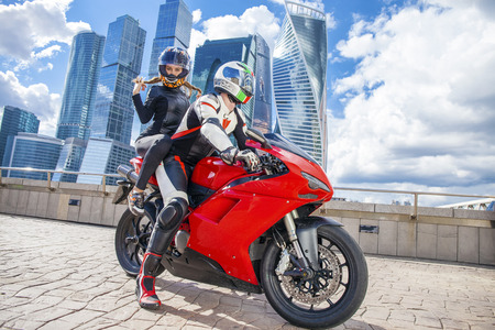 moto gp: Couple in a suit with a motorcycle sport bike on the background of urban high-rise buildings Stock Photo