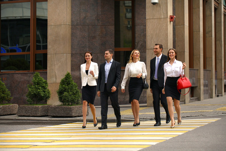 footpath: Full length portrait of a young Five successful business people crossing the street in the city center