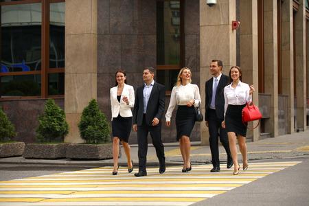 personas caminando: Retrato de cuerpo entero de un joven Cinco hombres de negocios exitosos que cruzan la calle en el centro de la ciudad Foto de archivo
