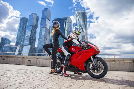 casco rojo: Pareja en un traje con una moto deportiva de la motocicleta en el fondo de los rascacielos urbanos Foto de archivo
