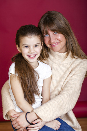 seven year old: Portrait of seven year old daughter and young mother on red isolated