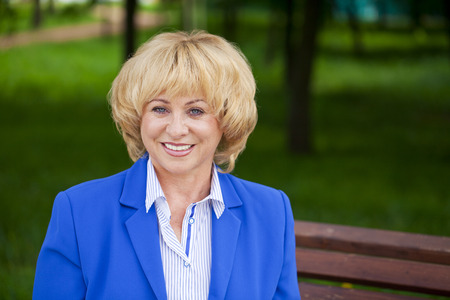 misses: Close up portrait of a beautiful middle aged woman in a blue business suit