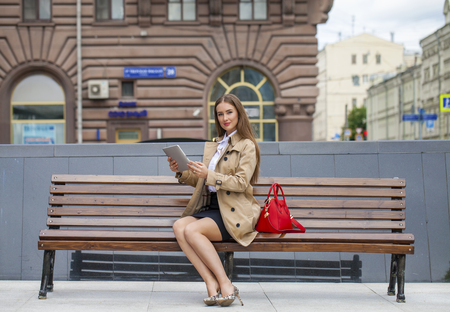 decides: Young beautiful business woman sitting on a bench in the summer city