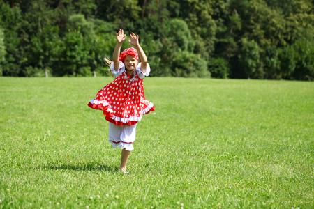 sundress: Little girl in a red polka-dot sundress into a major run on green field Stock Photo