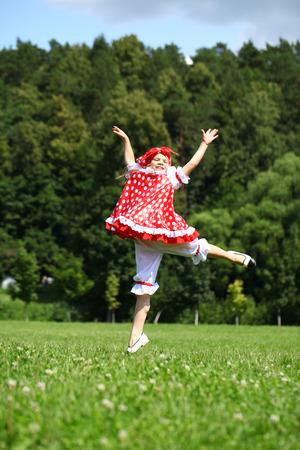 champ vert: Petite fille dans une robe d'�t� rouge de sauter de joie sur un champ vert