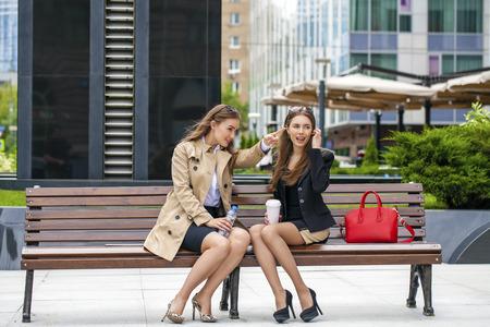 Twee jonge mooie zakelijke vrouwen zitten op een bankje in de zomer stad