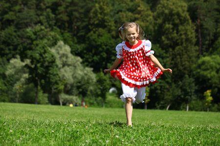 champ vert: Petite fille dans une robe � pois rouge dans une course majeure sur le terrain vert