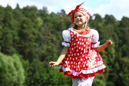 champ vert: Little girl in a red polka-dot sundress into a major run on green field Banque d'images