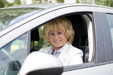 Beautiful old happy elderly driver woman 55-60 years in jacket Driving a Car Stock Photo