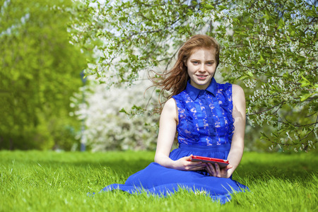 18's: Beautiful young girl reading notebook under the flowering white apple tree