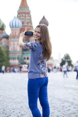 sights of moscow: Happy young brunette woman photographed attractions in Moscow