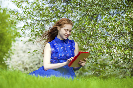 foxy girls: Beautiful young girl reading notebook under the flowering white apple tree