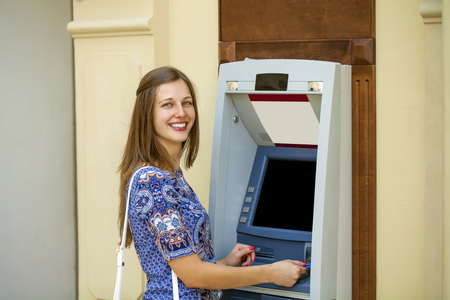 automated teller: Brunette young lady using an automated teller machine. Woman withdrawing money or checking account balance Stock Photo