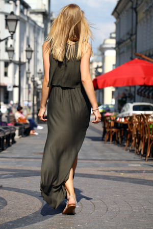 sensuous: Portrait in full growth, attractive young blonde woman in long dress walking in summer street