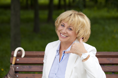 call me: Happy smiling old blonde woman with call me gesture, against green sunner park Stock Photo