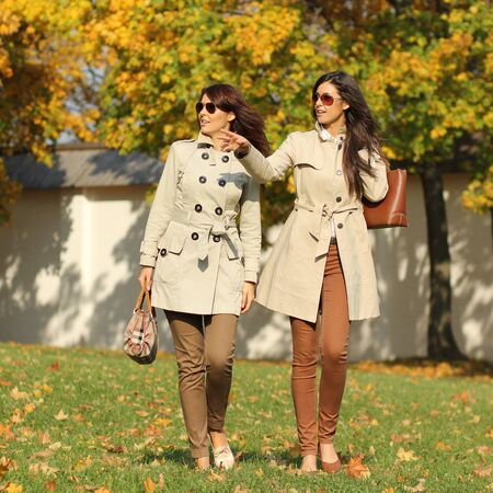 attractive women with autumn maple leaves in park at fall outdoors photo