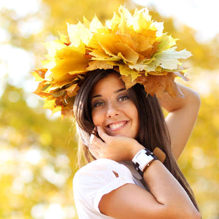 young beautiful girl with a bouquet of maple leaves photo