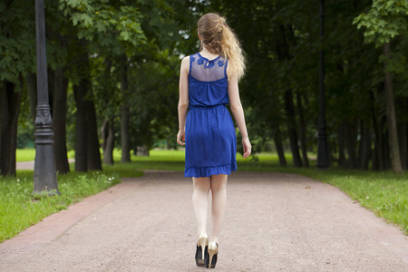 blue dress: Portrait in full growth, attractive young blonde woman in blue dress walking in summer park
