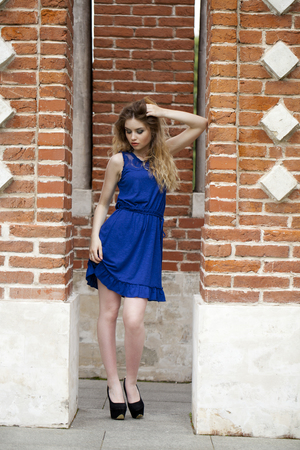 blue dress: Portrait in full growth, attractive young blonde woman in blue dress against the brick wall