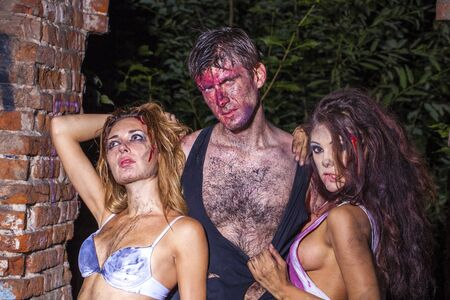 bloodied: One man and two bloodied girl in lingerie on the background of a brick wall Stock Photo