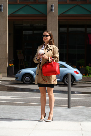 red bag: Portrait in full length, young business woman in a white shirt with red bag going to work